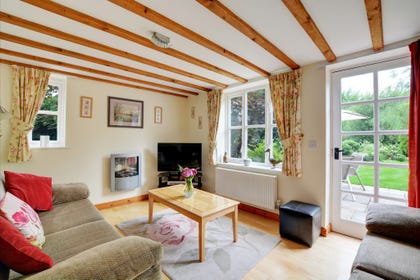 Contemporary sitting room with comfortable seating, beamed ceiling, wood floor and an electric fire for cosy evenings