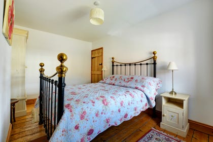 Delightful double bedroom with wrought iron double bed and pine floorboards