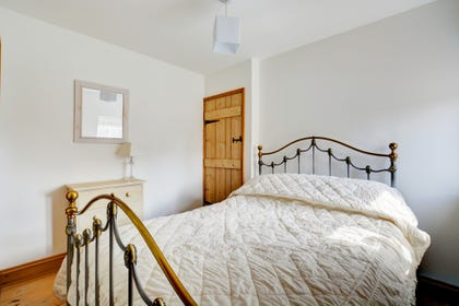 Pretty double bedroom with wrought iron double bed, feature fireplace and pine floorboards