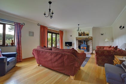 Light and spacious sitting room with large wood burner and french doors to the garden