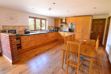Spacious kitchen dining area has a full range of  lovely wooden units and a table that comfortably seats seven for family meals