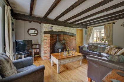 The sitting room oozes character with exposed ceiling beams and a large fire place with a woodburner for cosy evenings