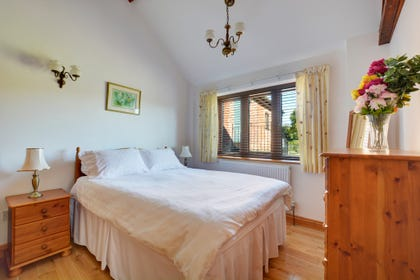 Charming double bedroom with double bed and pine furniture for storage