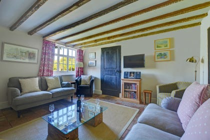 The sitting room has a traditional inglenook fireplace with an electric wood-burning effect stove, beams and pamment floor