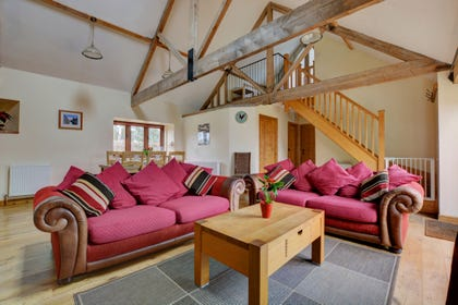 View of the comfortable sitting room with large colourful sofas and open beams.  Coffee table between sofas for drinks and books.  Open plan stairs to first floor.