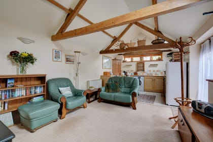 The sitting room has comfortable seating a beamed vaulted ceiling.