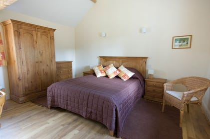 This shows the main bedroom with vaulted ceiling, king size bed en-suite shower room