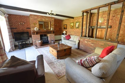 Showing the wonderful original beams and feature fireplace with traditional wood burning stove