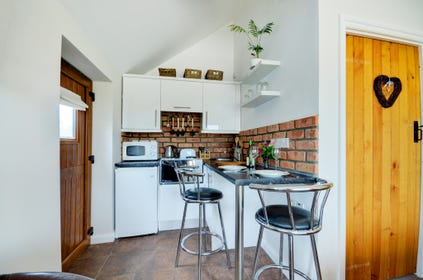 The kitchen area includes a handy breakfast bar and stools.