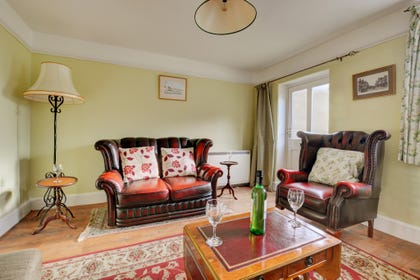 A comfortable sitting room that has a widescreen TV, DVD and CD player and open fire.