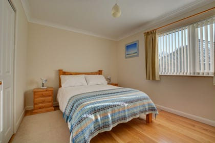 Spacious double bedroom with wooden floor.