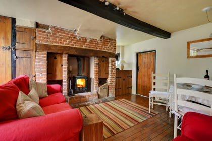 Sitting Room has comfortable seating beside the woodburner and  has a flatscreen TV with Freeview, video, DVD player, CD hi-fi.