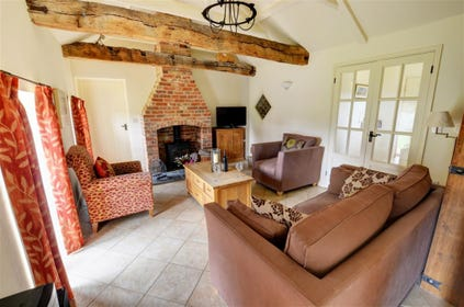 This beautiful sitting room has comfortable seating and a woodburner