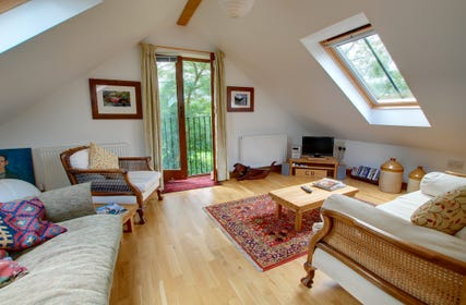 With wooden floor and velux window and doors to balcony.