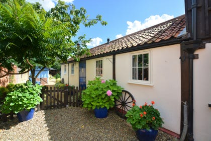 Pretty front view, with gravelled pathway, picket fencing and small tree.