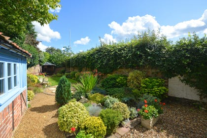 Very pretty walled garden with rockery and gravelled pathway leading to further garden and lawn area.