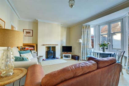 First floor sitting room with comfy seating and a woodburner