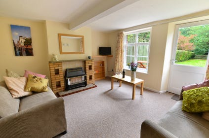The sitting room is comfortably furnished and has a gas fire in a feature fireplace.