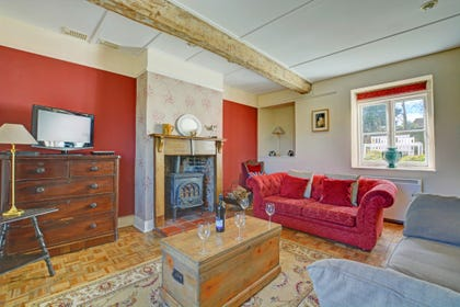 Spacious sitting room with comfortable seating and a traditional woodburner