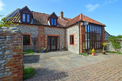 Rear exterior of this attractive brick and flint barn conversion