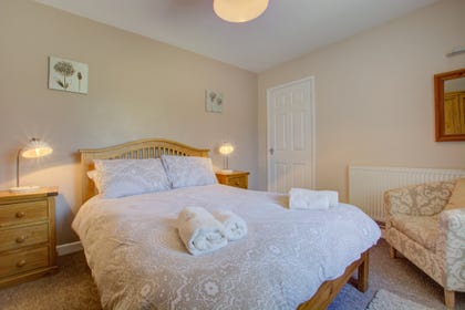 A comfortable double bedded room with television and plenty of storage space.