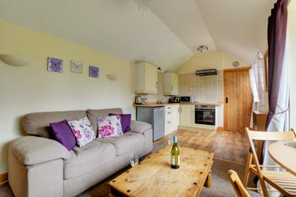 Open plan sitting room with comfortable seating and a dining area, giving a feeling of space