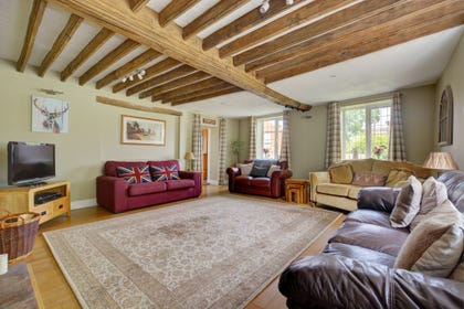 Large sitting room, comfortable seating, TV, open beams