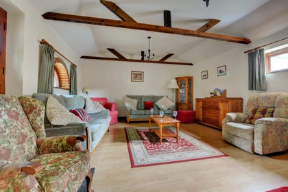 Spacious and light sitting room with a feature fireplace, exposed brickwork and lovely beams