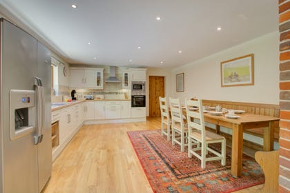 White fronted cupboards, stainless steel cooker and hob. Large dining table on rug on wooden floor.