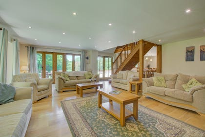 Another view of sitting room showing open-plan staircase and patio doors to garden.
