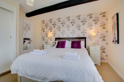 Double bed with bedside cabinets & lighting. Beam in ceiling shows character of property.