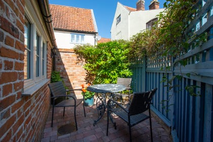 Pretty courtyard with garden furniture, pots of geraniums and bright blue wooden fence.