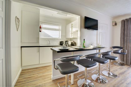 Fitted and equipped kitchen with breakfast bar and stools