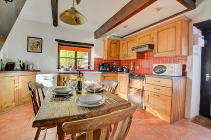 Large farmhouse kitchen with most major appliances and lovely character beams and tiled floors
