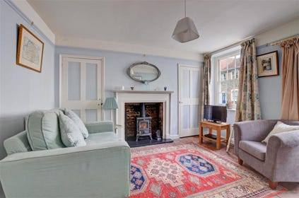View of sitting room in true cottage style, comfortable chairs by the fireside, a true cosy retreat.